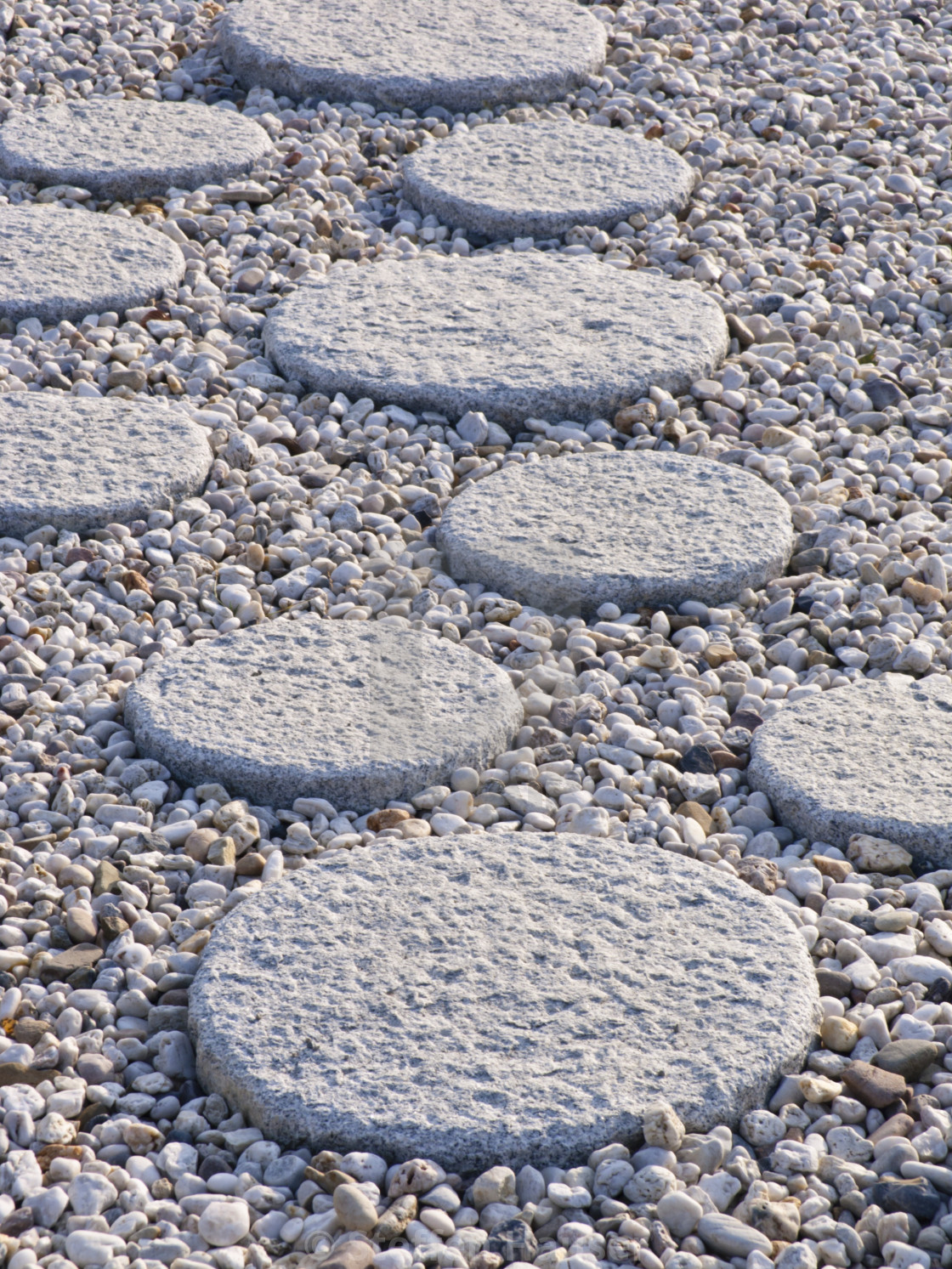 Round hewn path slabs in different sizes in a gravel bed
