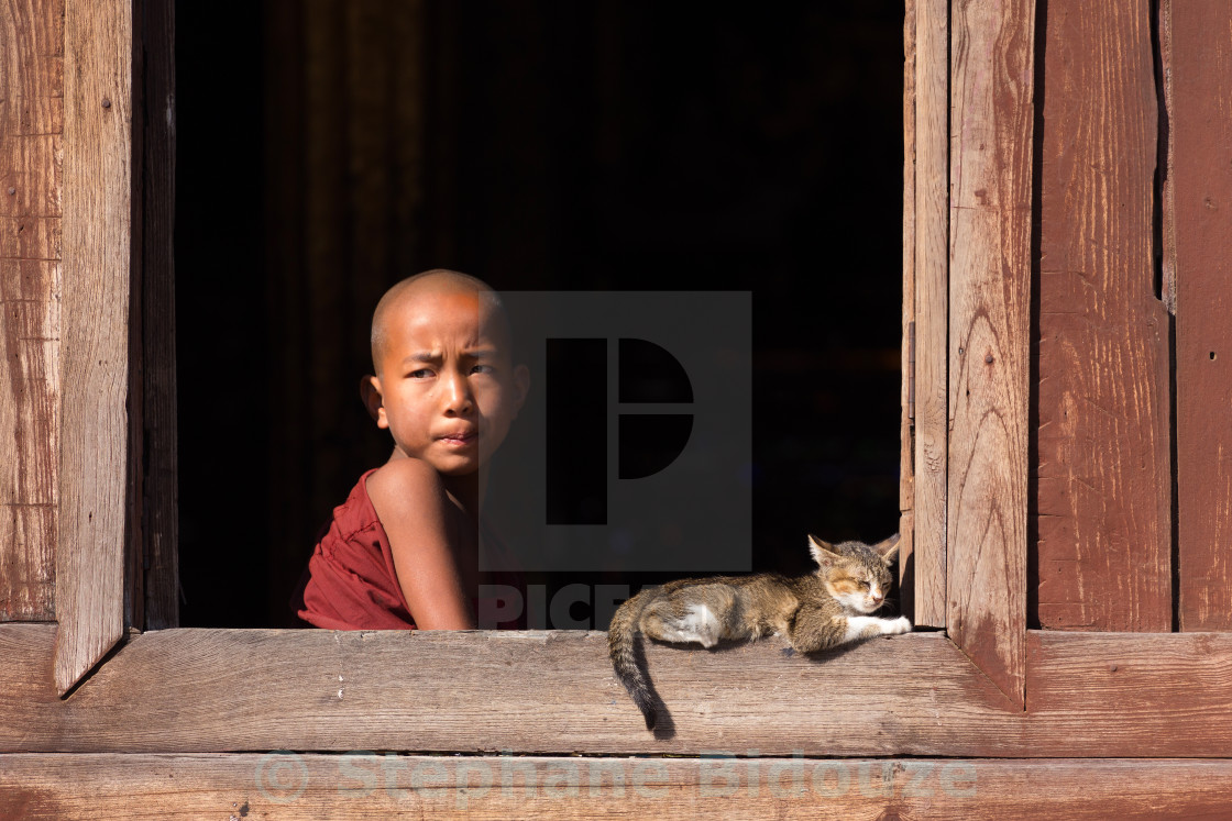 """Young buddhist monks laughing at a window"" stock image"