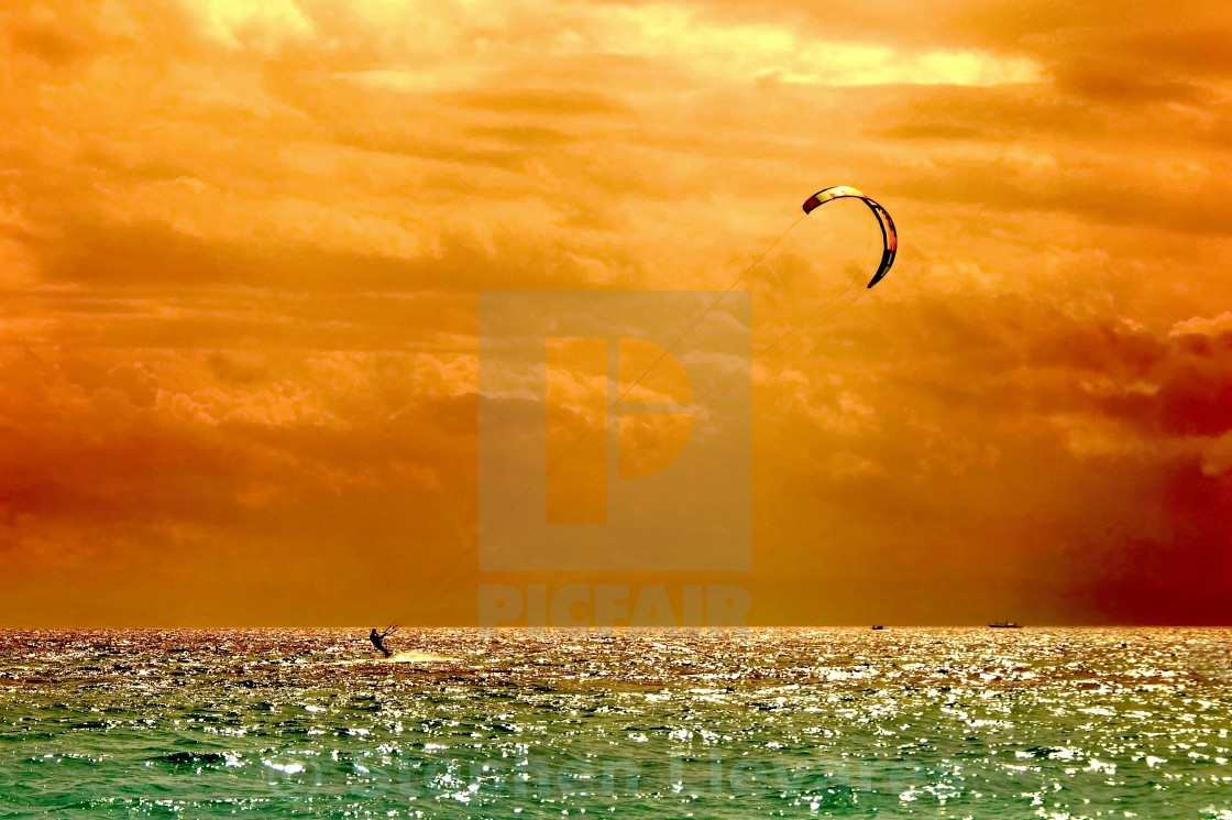 """Parasailing Fun Under a Fiery Sky"" stock image"