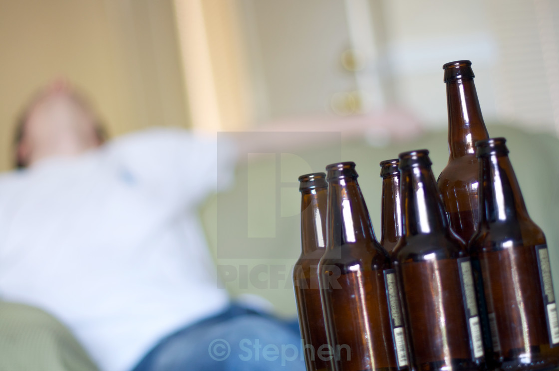 """Man passed out on couch with empty beer bottles, angled"" stock image"