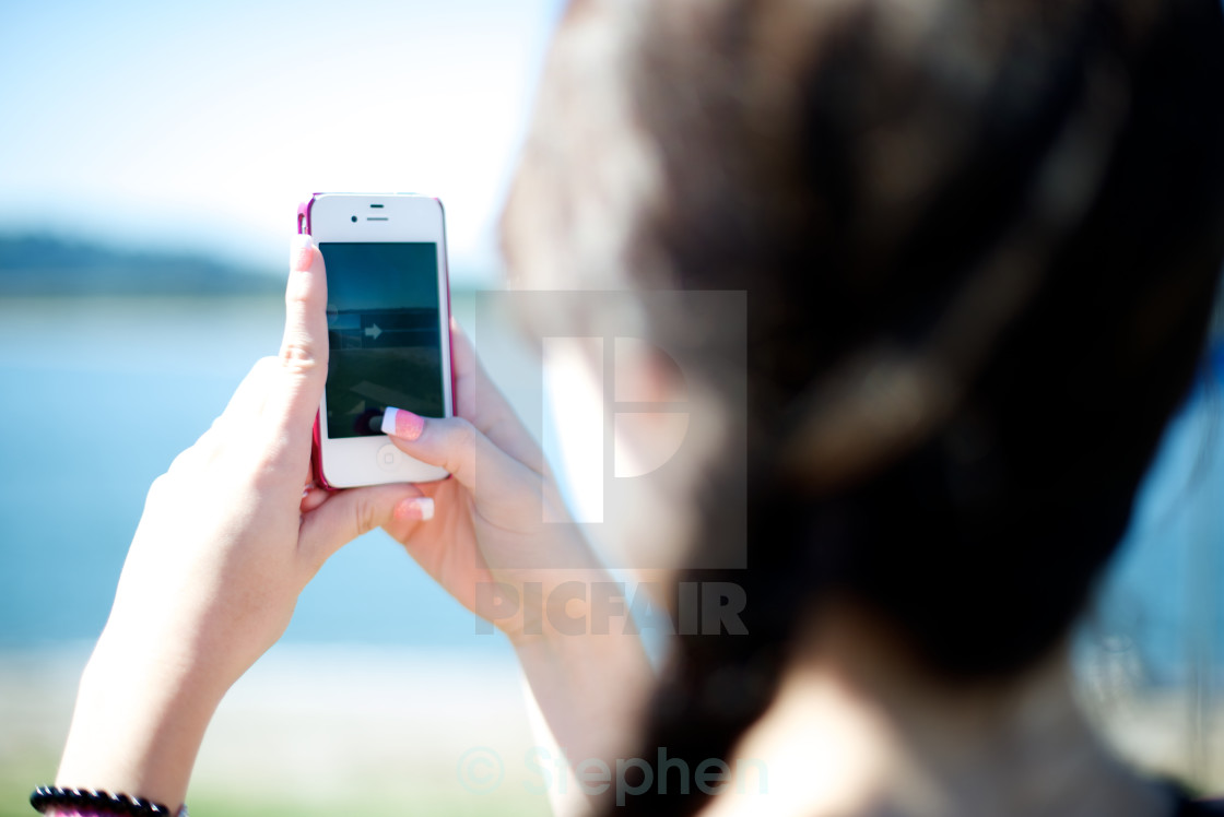 """""""Girl takes a picture of scenary with her phone"""" stock image"""
