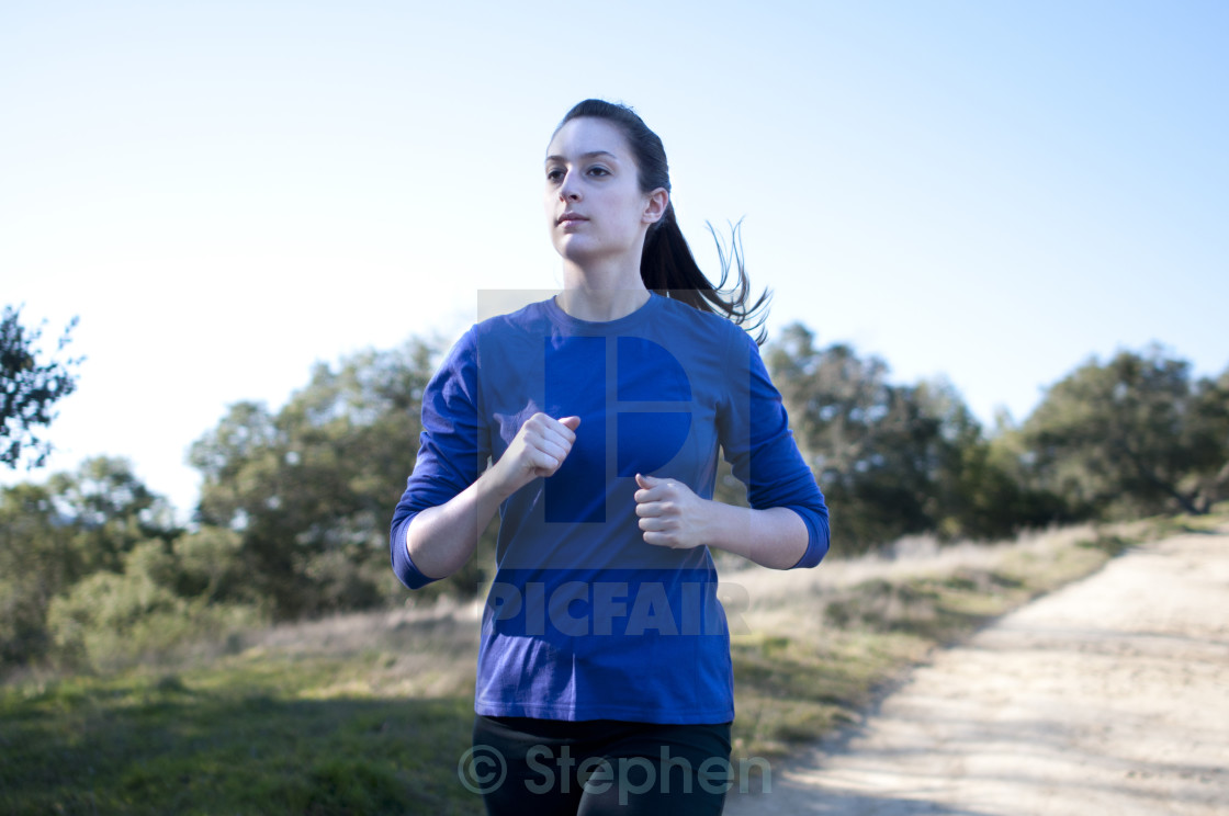 """""""Centered close up of woman jogging outside, facing left"""" stock image"""