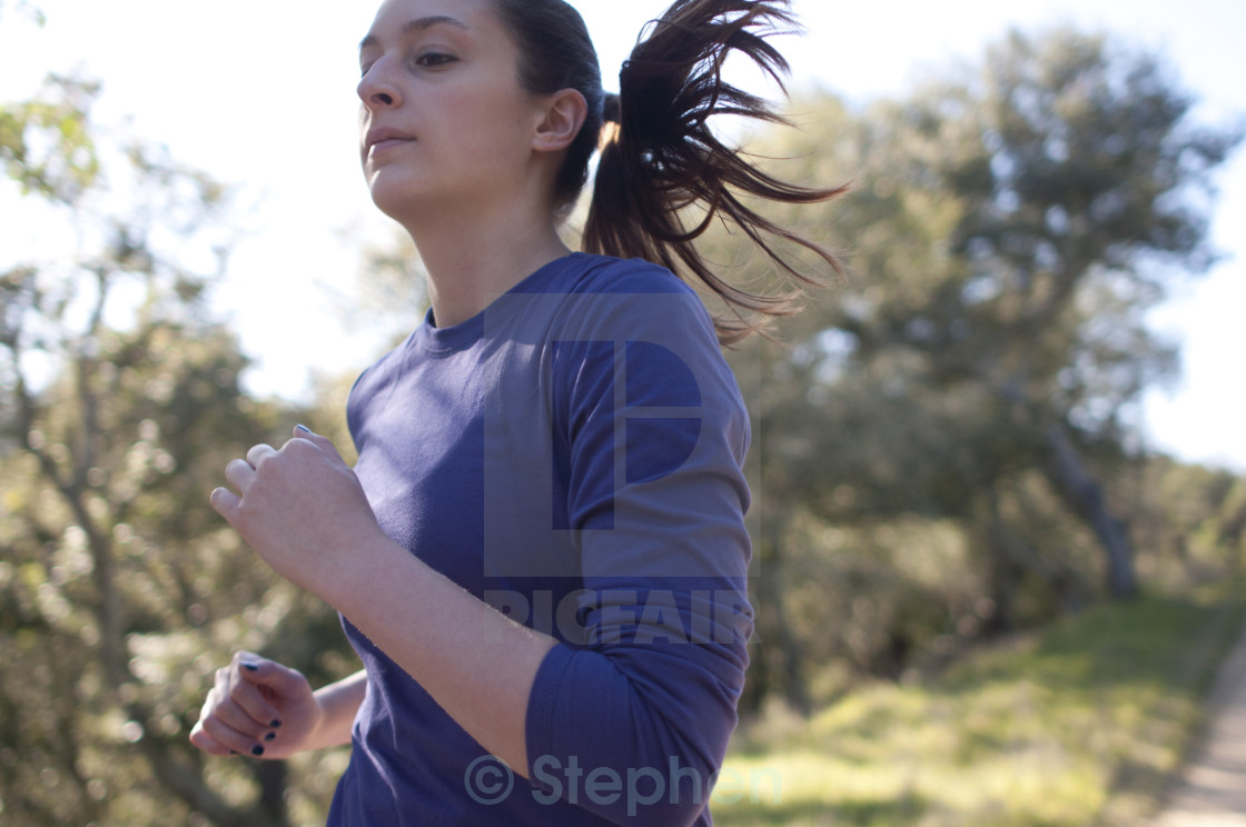 """""""Very close up of woman jogging, facing left"""" stock image"""