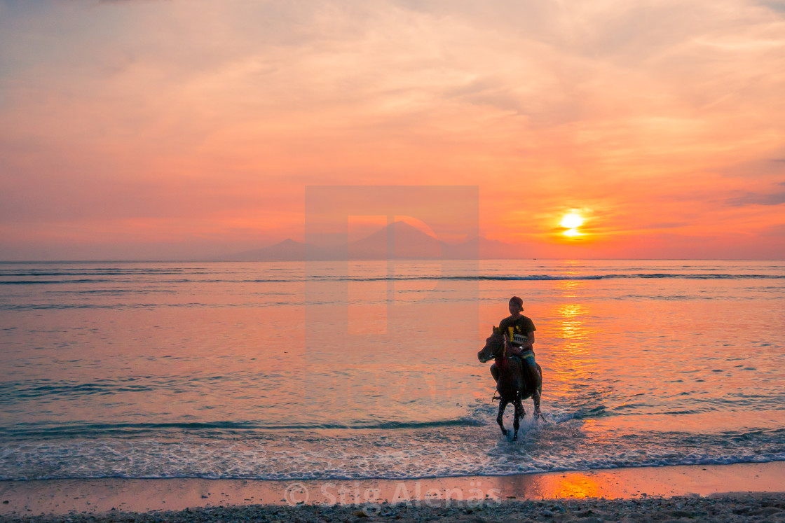 """An indonesian man riding in the water at sunset"" stock image"