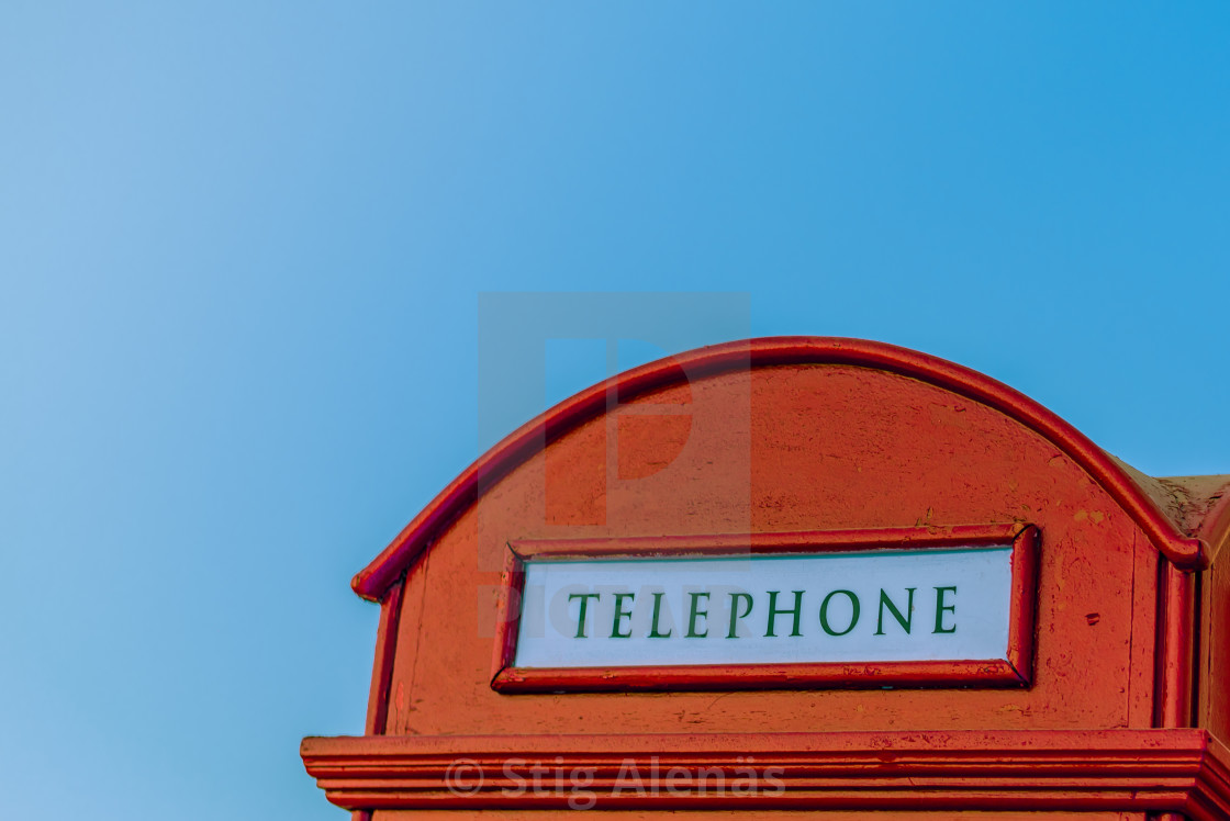 A red english call-box against the blue sky with space for texts