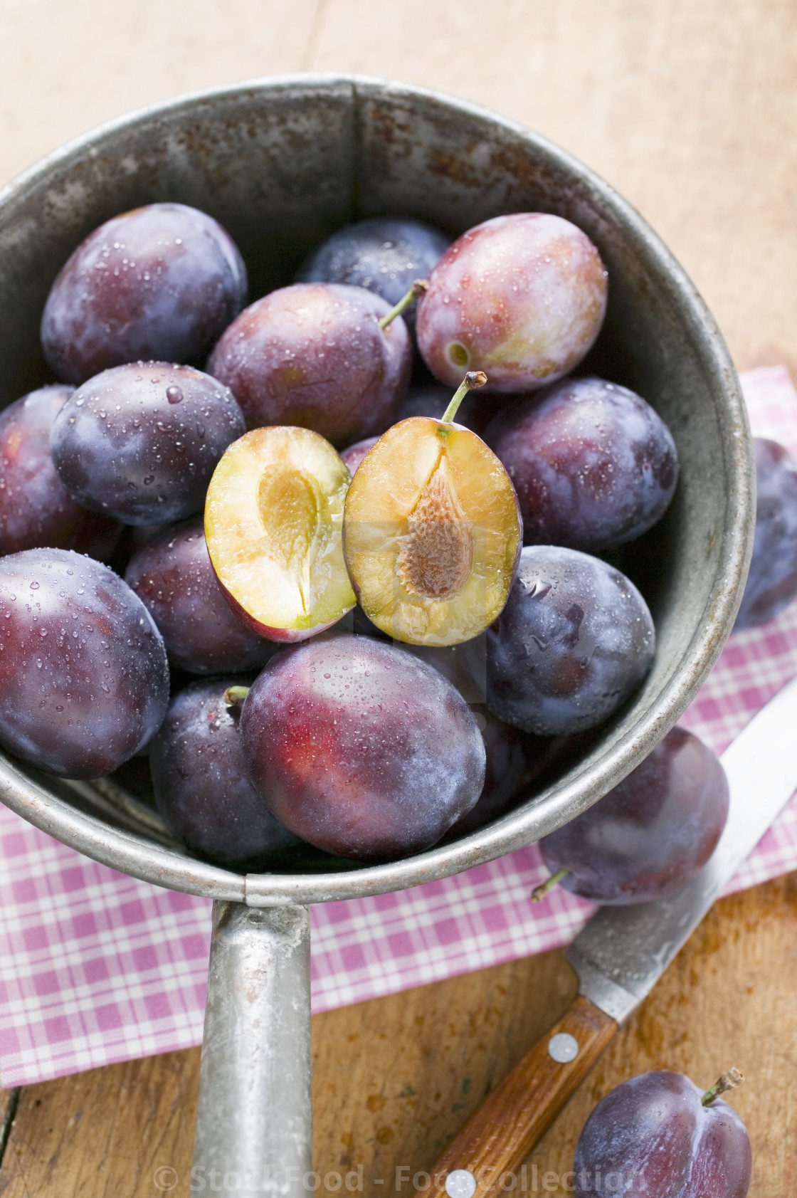 """Fresh damsons, one halved in metal strainer"" stock image"