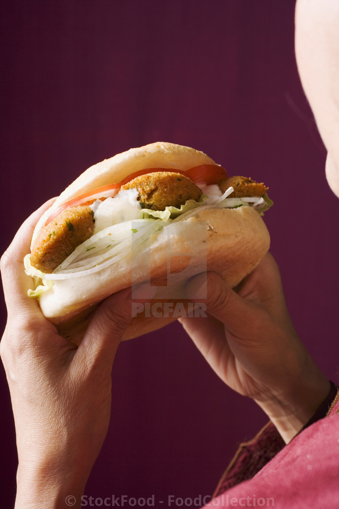 """""""Hands holding flatbread filled with falafel (chick-pea balls)"""" stock image"""