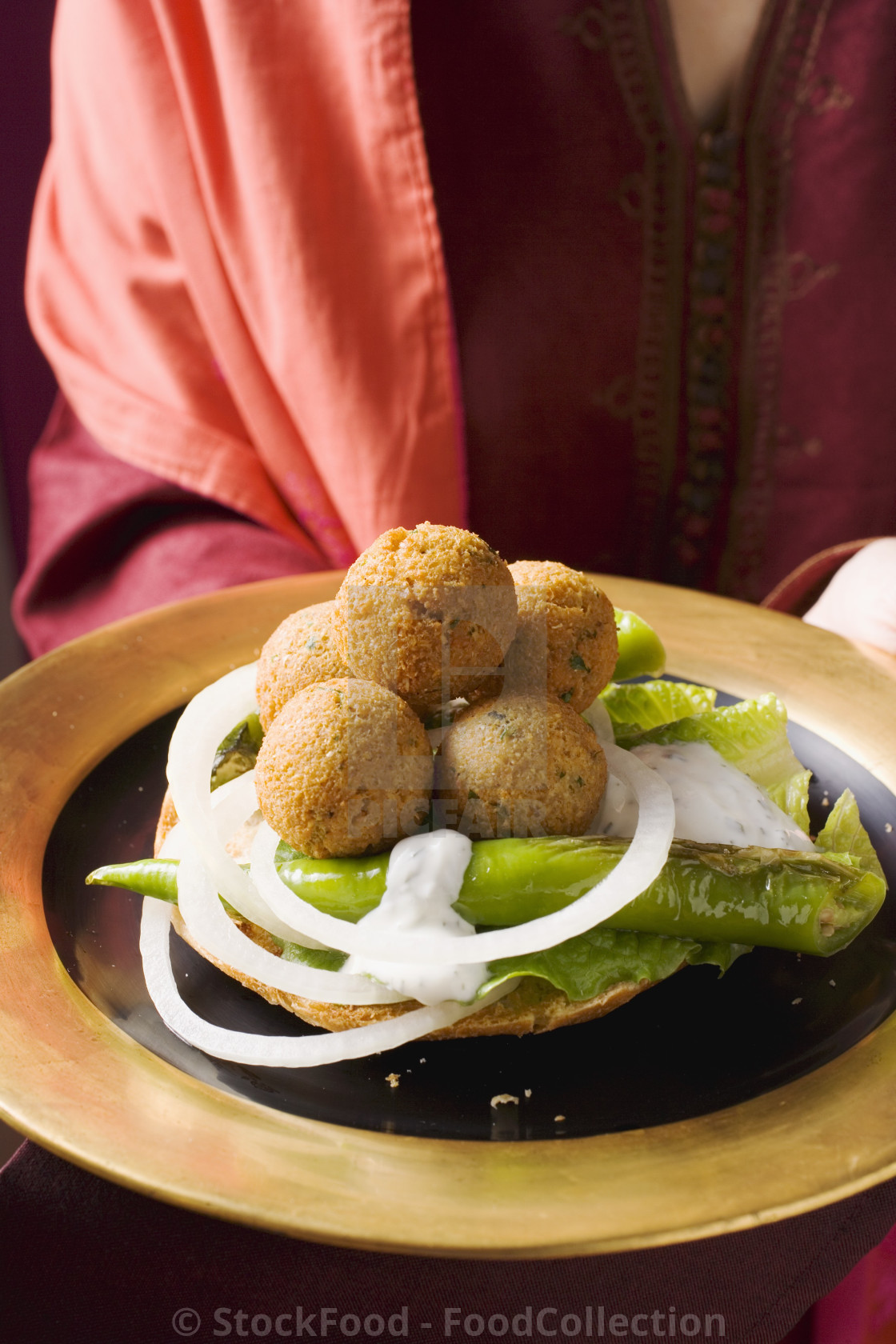 """""""Woman serving falafel (chick-pea balls) with vegetables"""" stock image"""