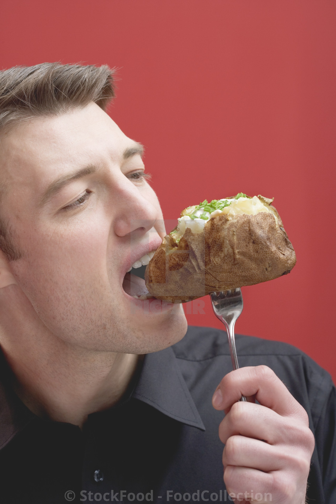Man eating baked potato - License, download or print for