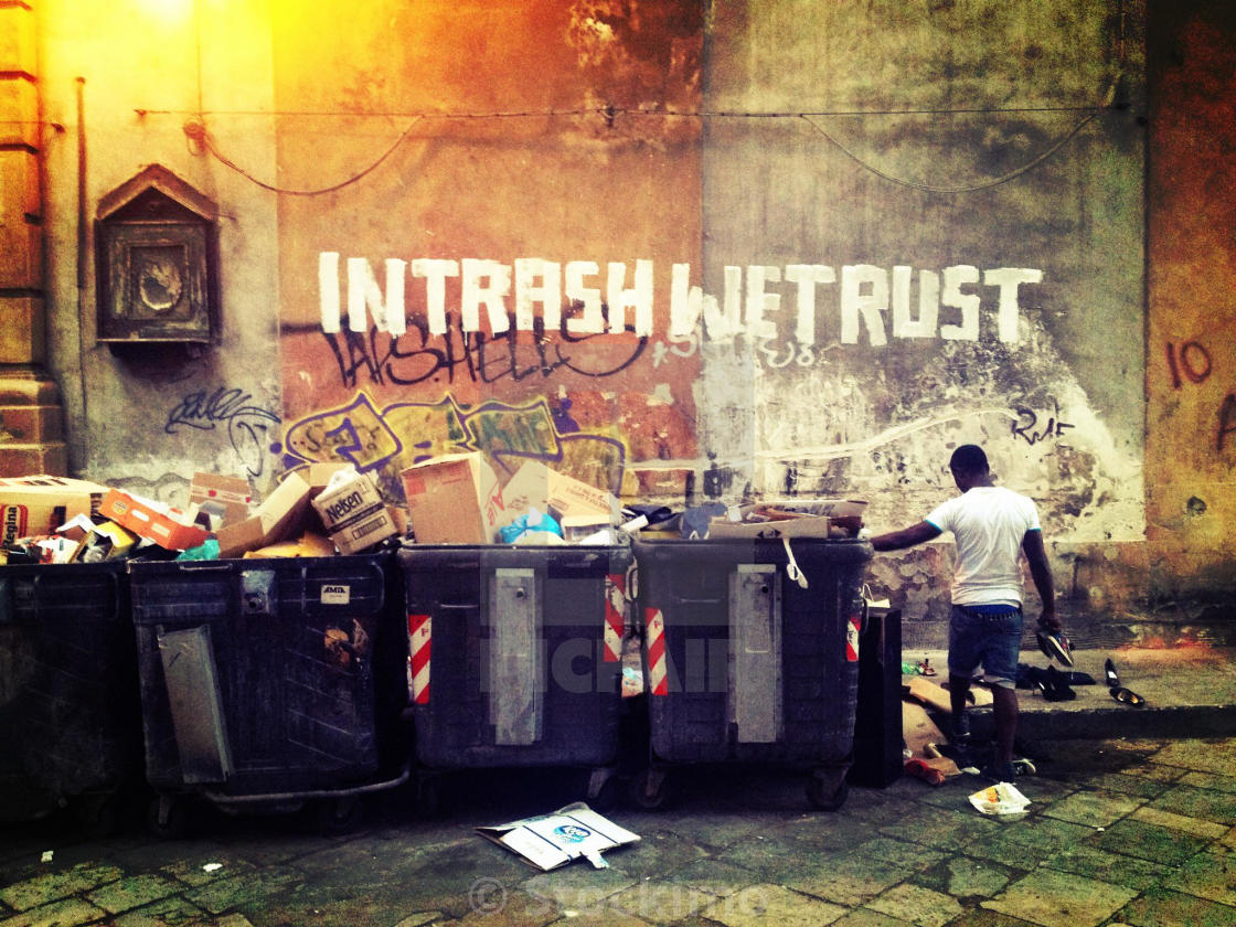 """Man Collecting things from the rubbish bin, on the wall: ""in trash we trust"", Palermo, Italy"" stock image"
