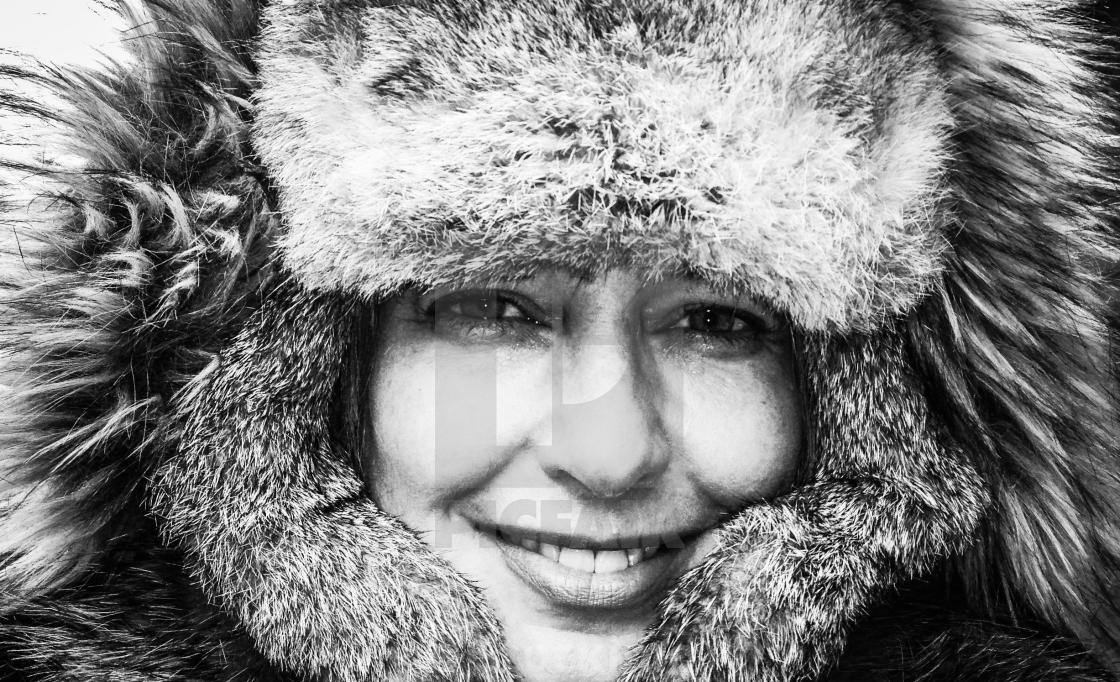 """""""In sub-zero weather a woman smiles as she tries to stay warm."""" stock image"""