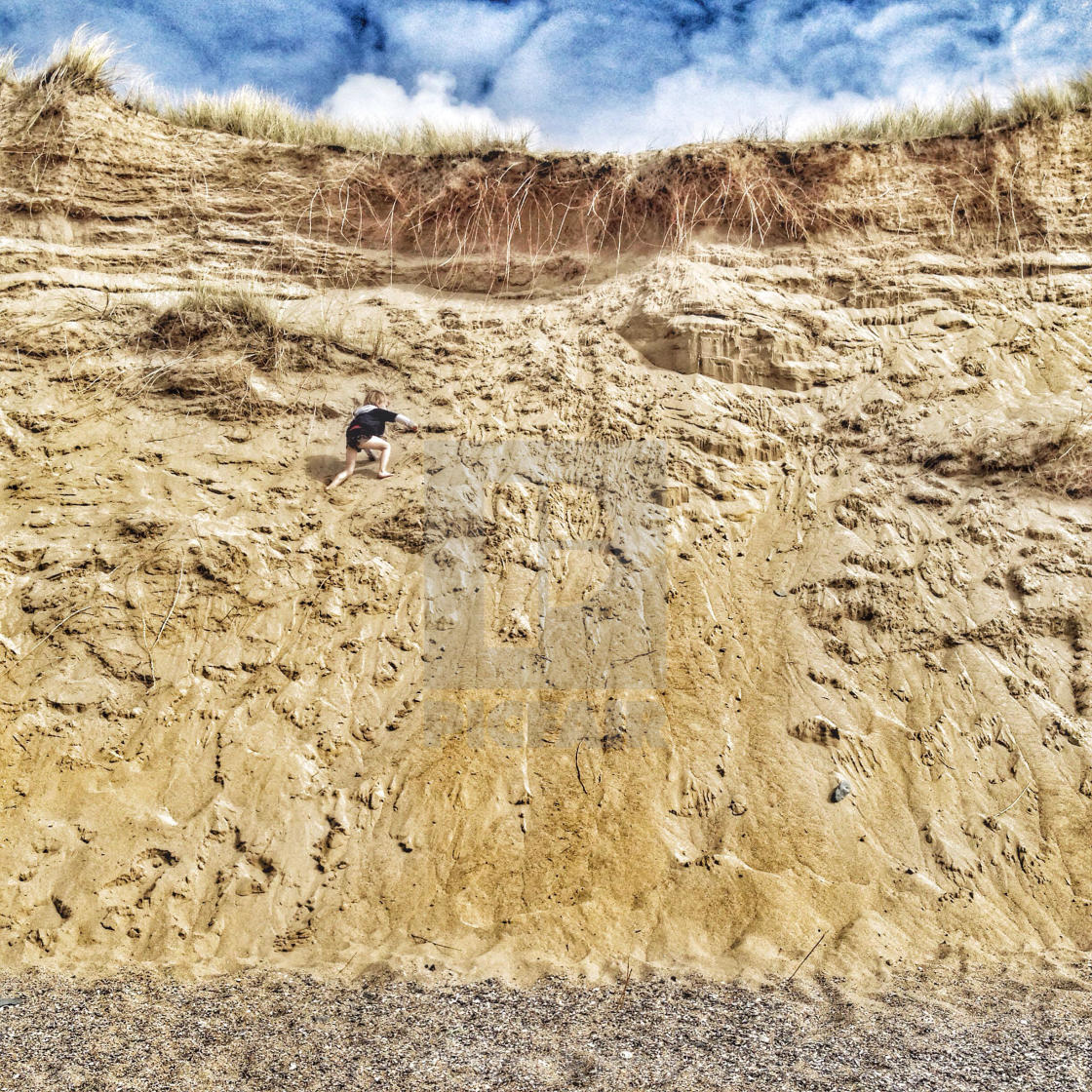 """Boy climbing the dunes at Holywell Bay in Cornwall"" stock image"
