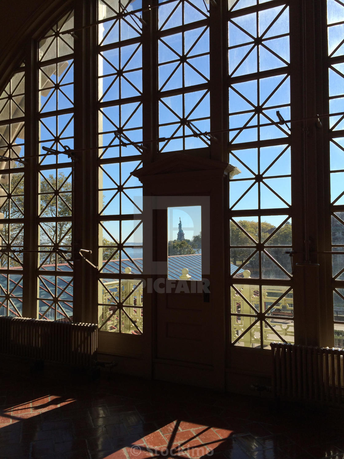 """""""A peek at the Statue of Liberty as seen from the Registration Room of the Ellis Island Immigration Museum in New York."""" stock image"""