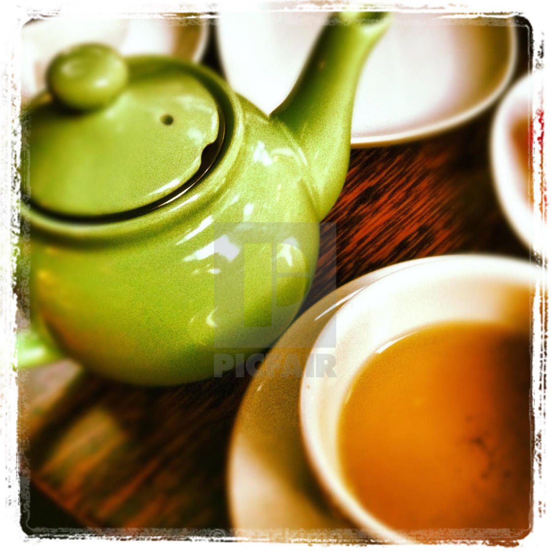"""""""Green tea pot and cup half full of tea on a wooden table."""" stock image"""