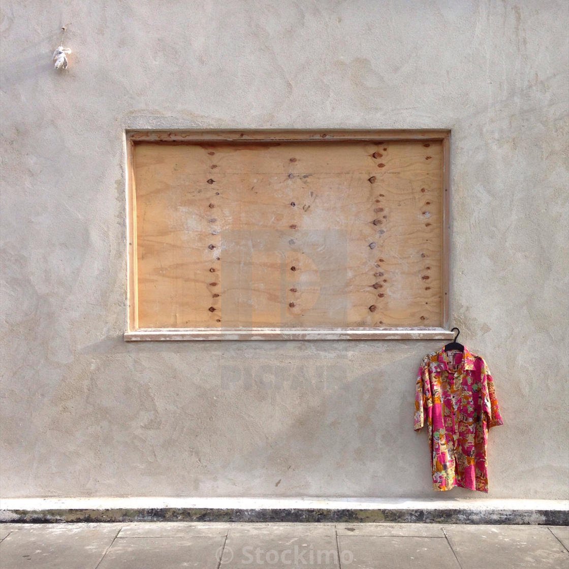 """A Hawaiian shirt hanging from a boarded up window in Clarence Rd, Hackney, London"" stock image"