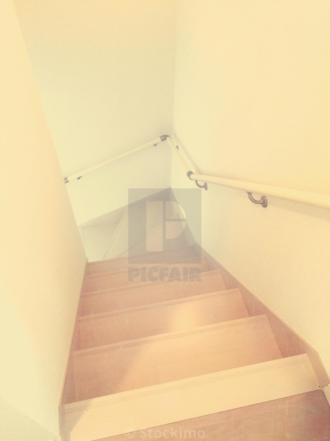 Simple, narrow staircase with light brown wood, white walls