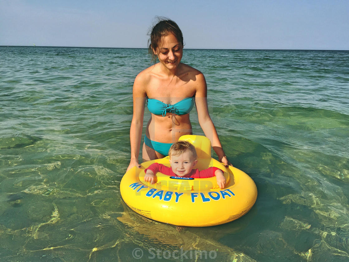 """""""Baby in inflatable ring with his mother"""" stock image"""