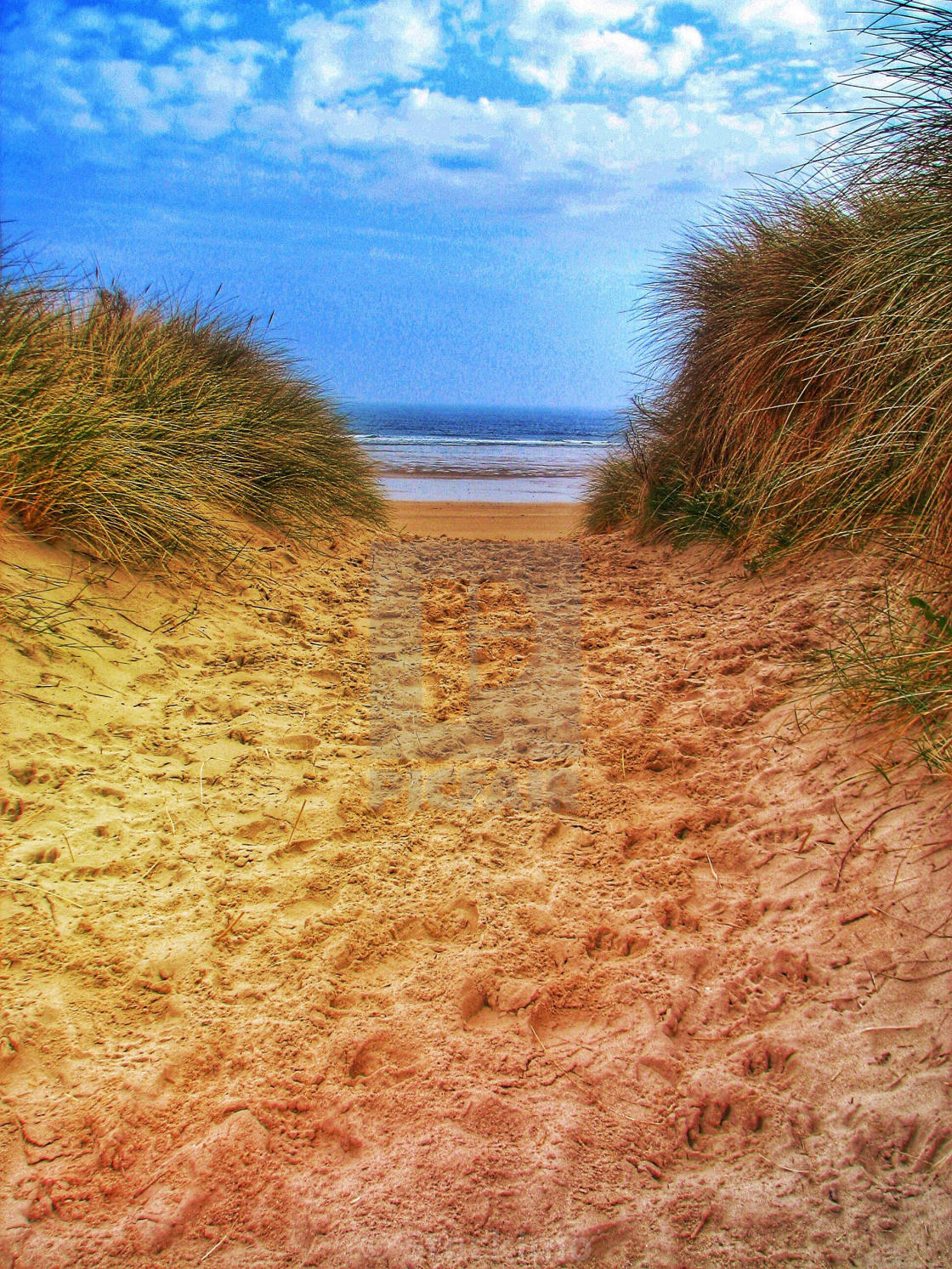 A sandy path through the sand dunes to a beautiful beach with an ...