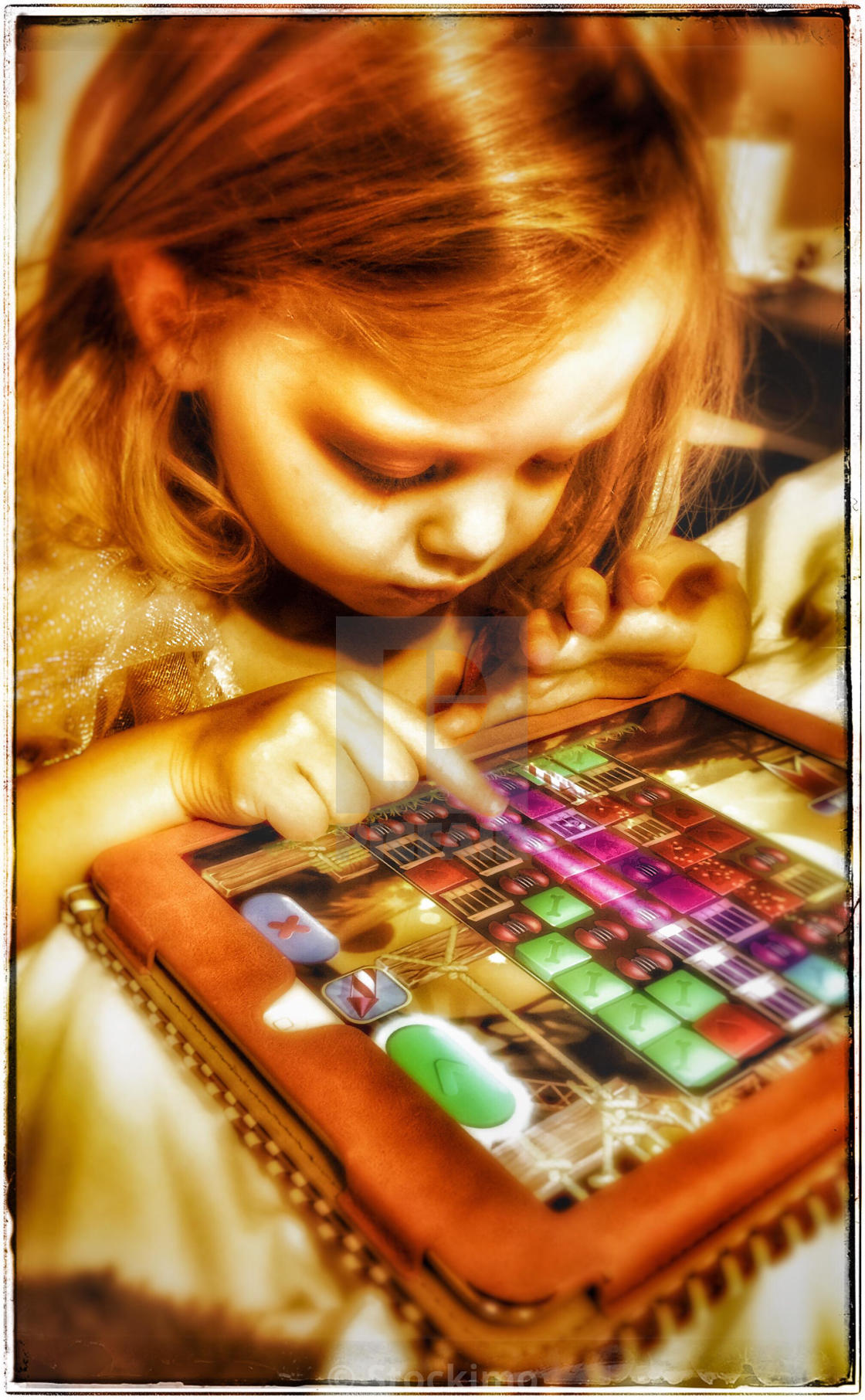 Little girl playing pet rescue saga on an iPad - License
