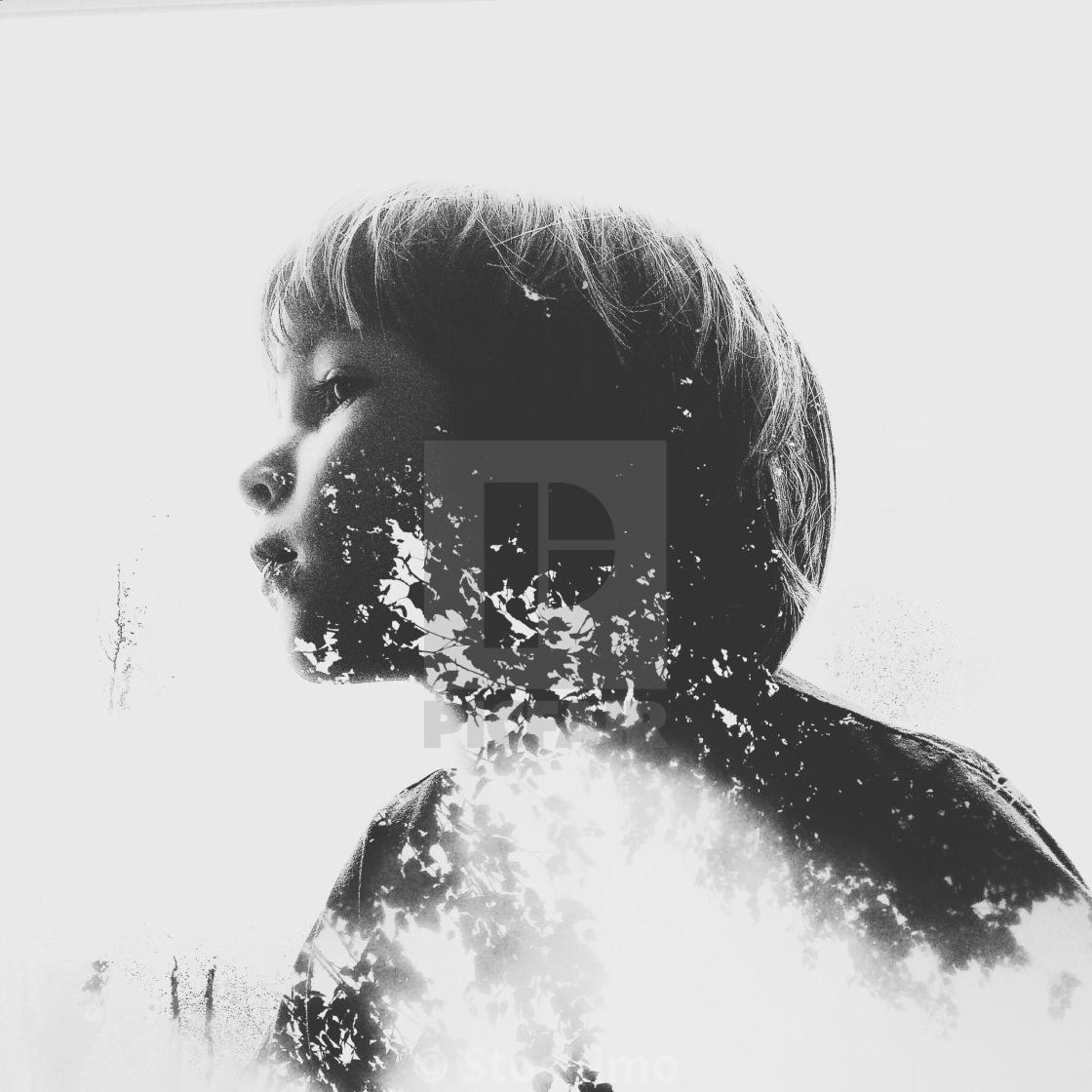 """Double exposure of young boy stares out of window on a rainy day."" stock image"