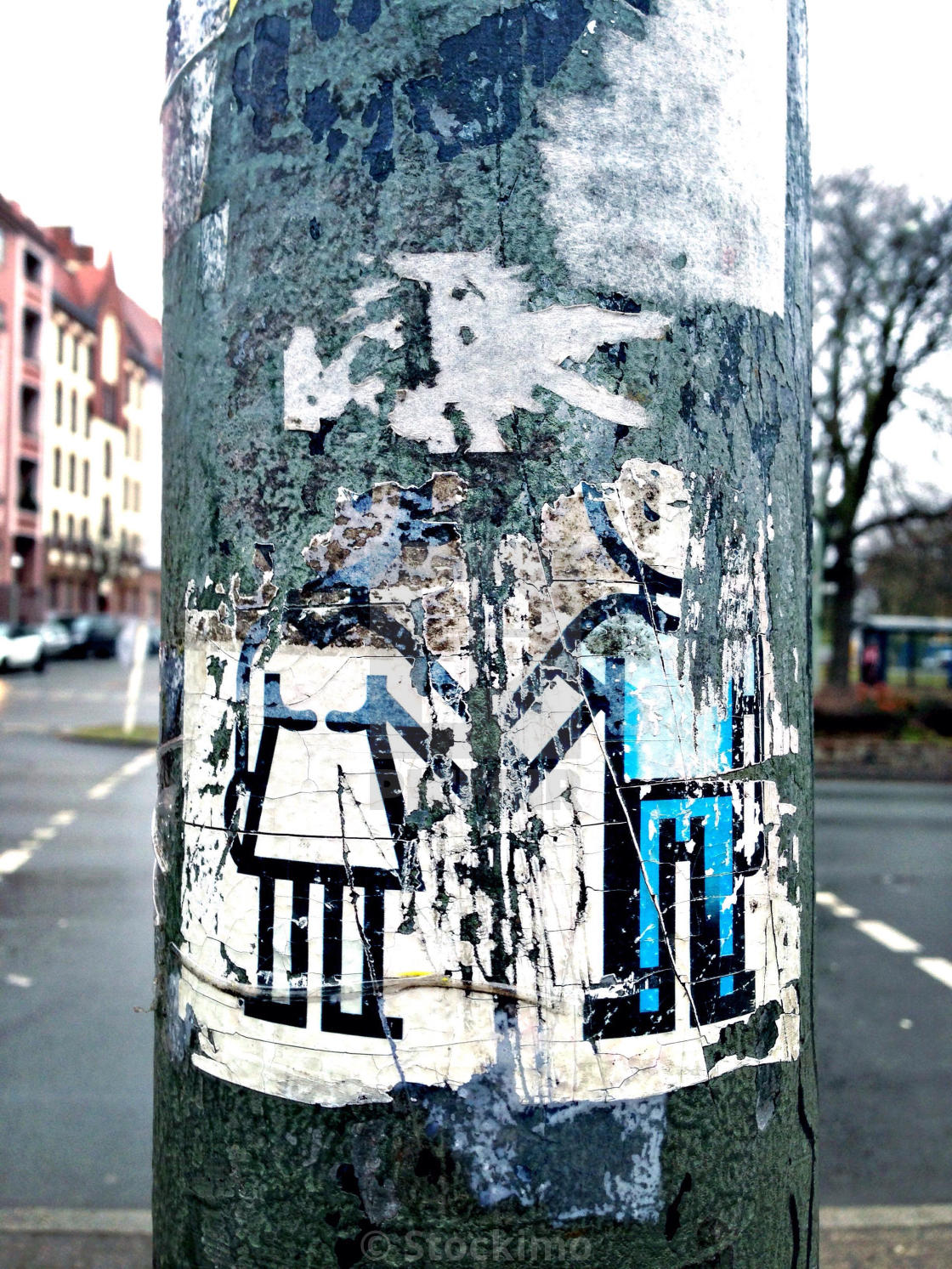 A street art sticker of a man and a woman holding hands on the pole