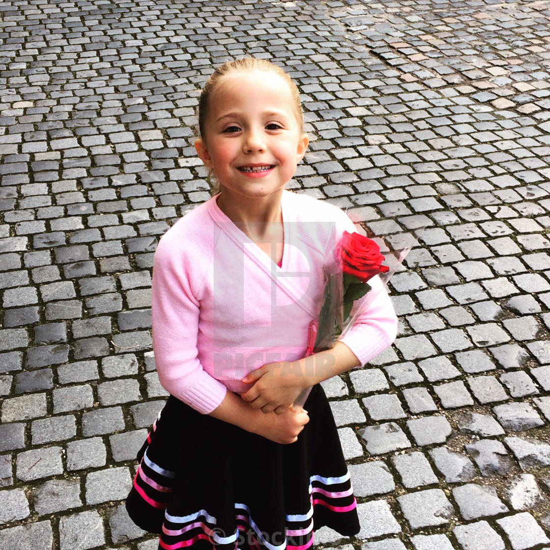 A young girl poses with a red rose after taking her grade 1