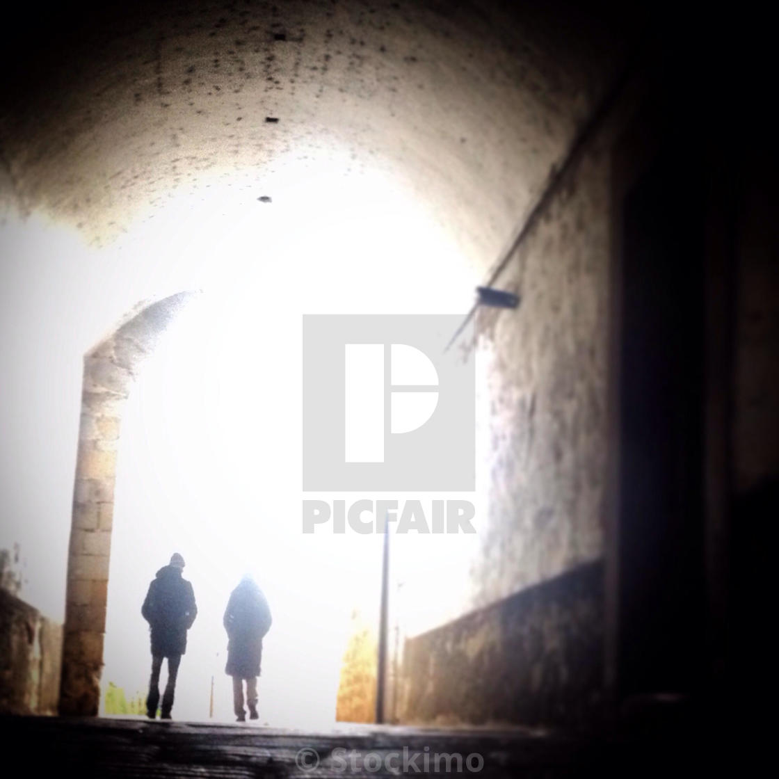 """""""A couple passes a tunnel in a street of Plasencia, Caceres, Extremadura, Spain"""" stock image"""