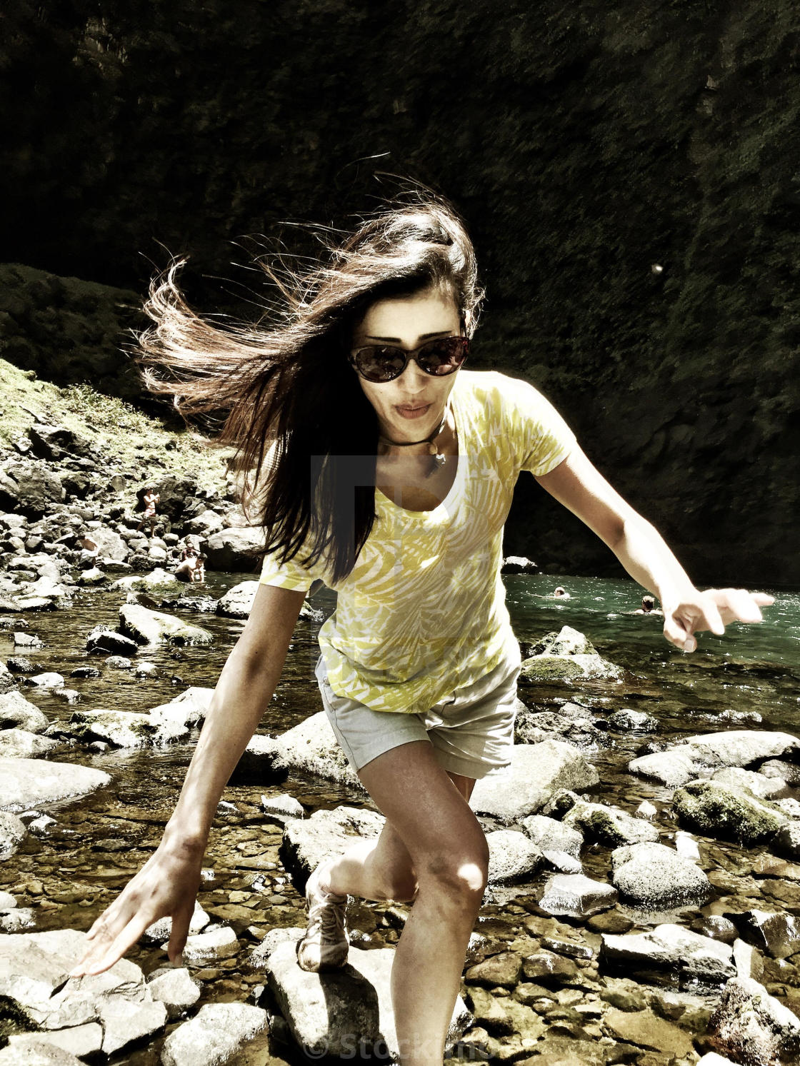 """Young woman, long brunette hair, glides gracefully balanced across river rocks"" stock image"