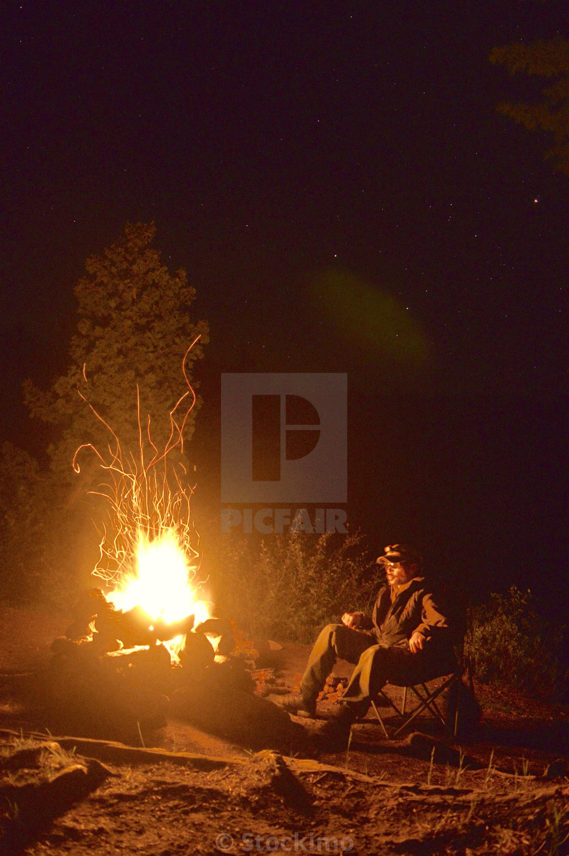Person In Chair Looking At Night Campfire License