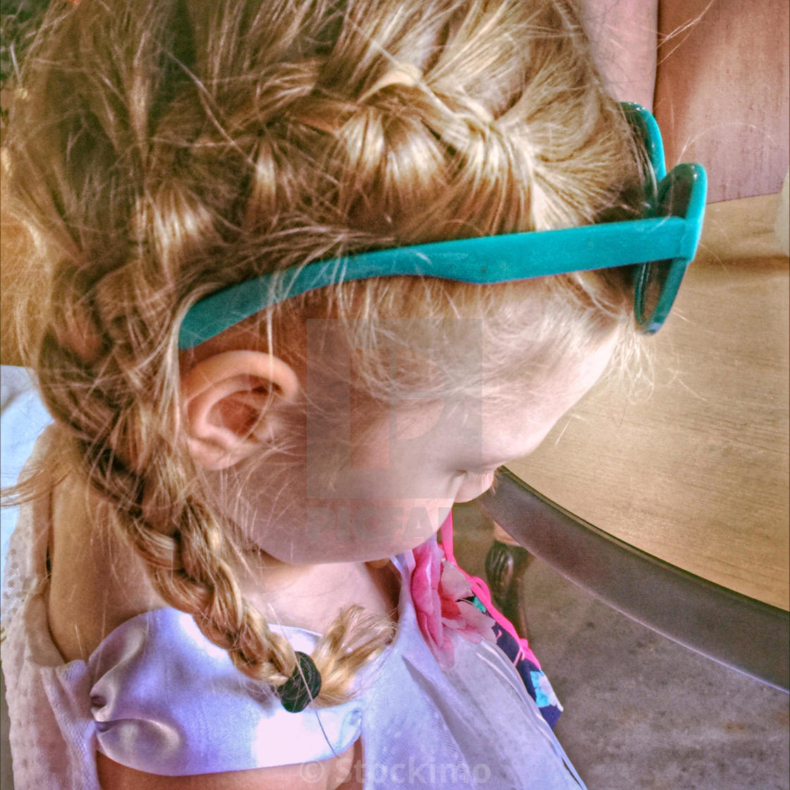 Side View Of A Little Girl In French Braid Pig Tails Wearing