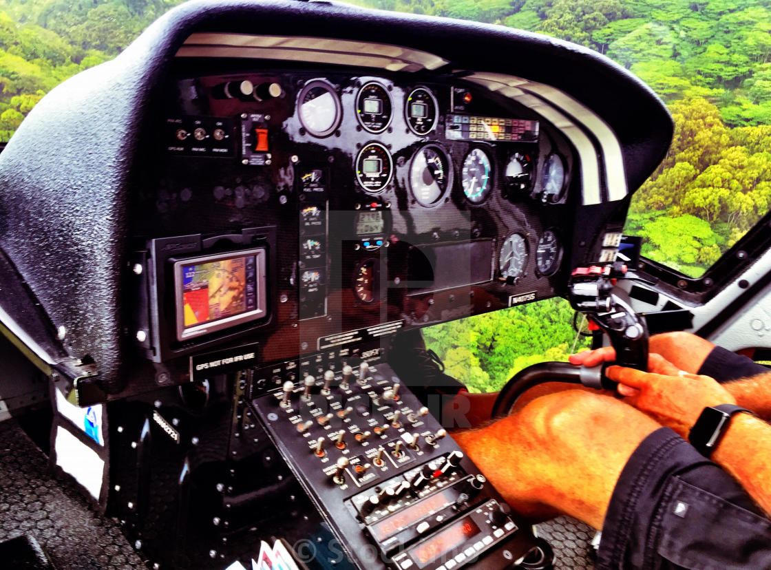 Helicopter flight dashboard and pilot over jungle canopy