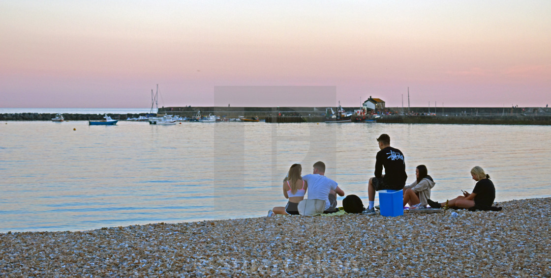 """""""Young Group on Lyme Regis Bay at Sunset"""" stock image"""