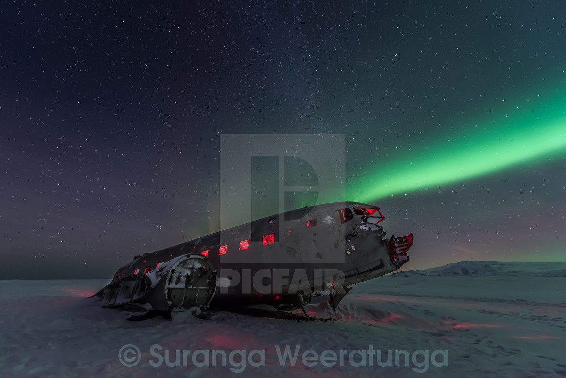 """Northern lights over plane wreck on the wreck beach in Vik, Iceland"" stock image"