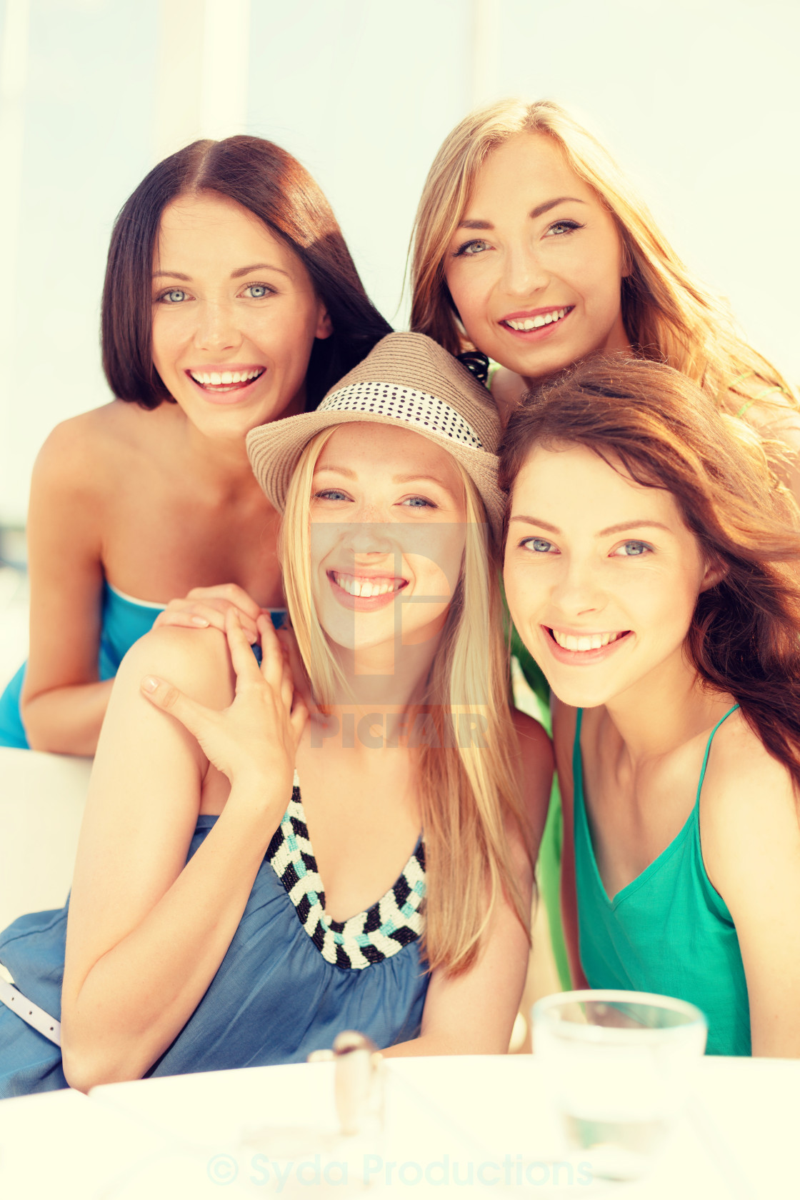 Group Of Smiling Girls In Cafe On The Beach License