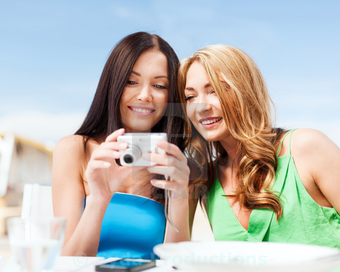 Girls With Camera In Cafe On The Beach License Download