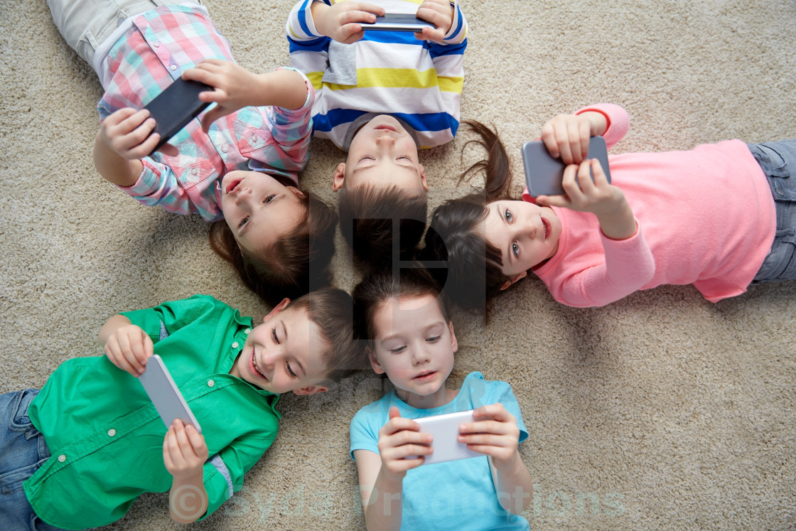 """happy children with smartphones lying on floor"" stock image"