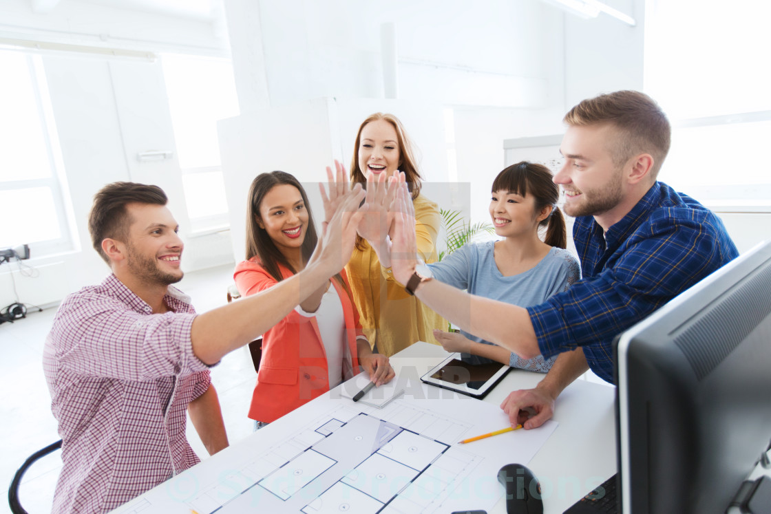 """""""creative team making high five at office"""" stock image"""