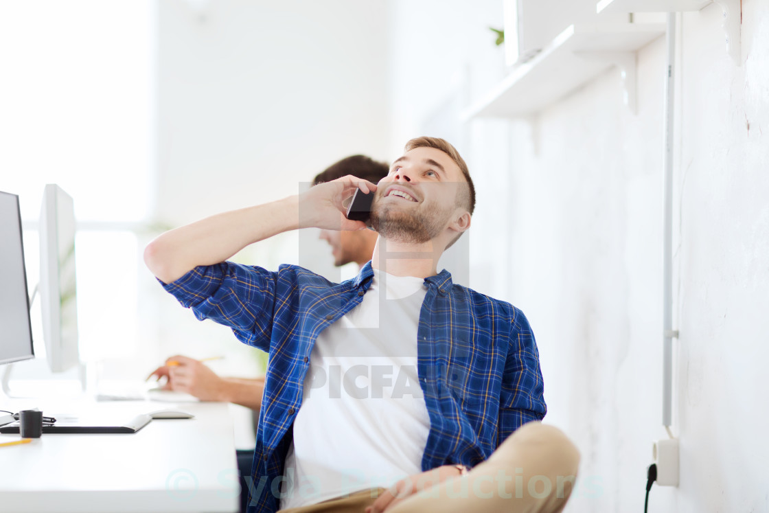 """happy creative man calling on cellphone at office"" stock image"