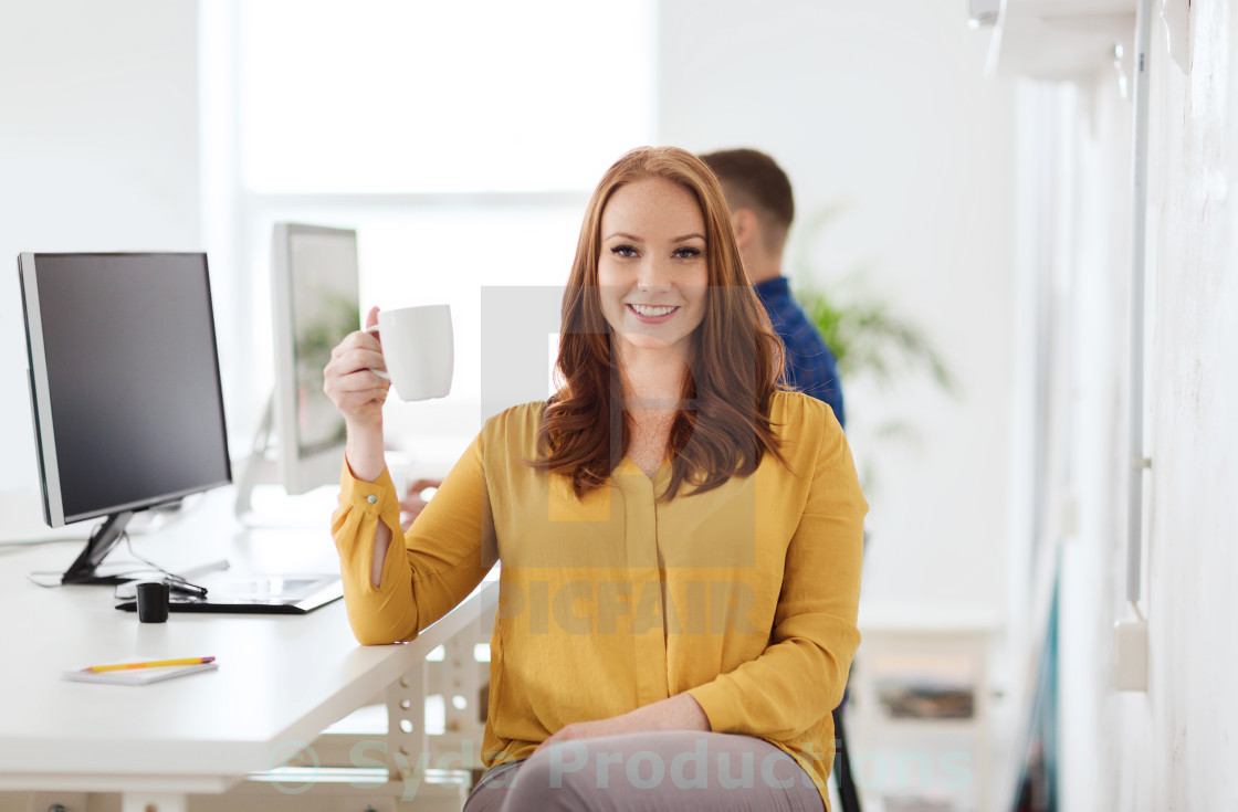 """happy woman drinking coffee or tea at office"" stock image"
