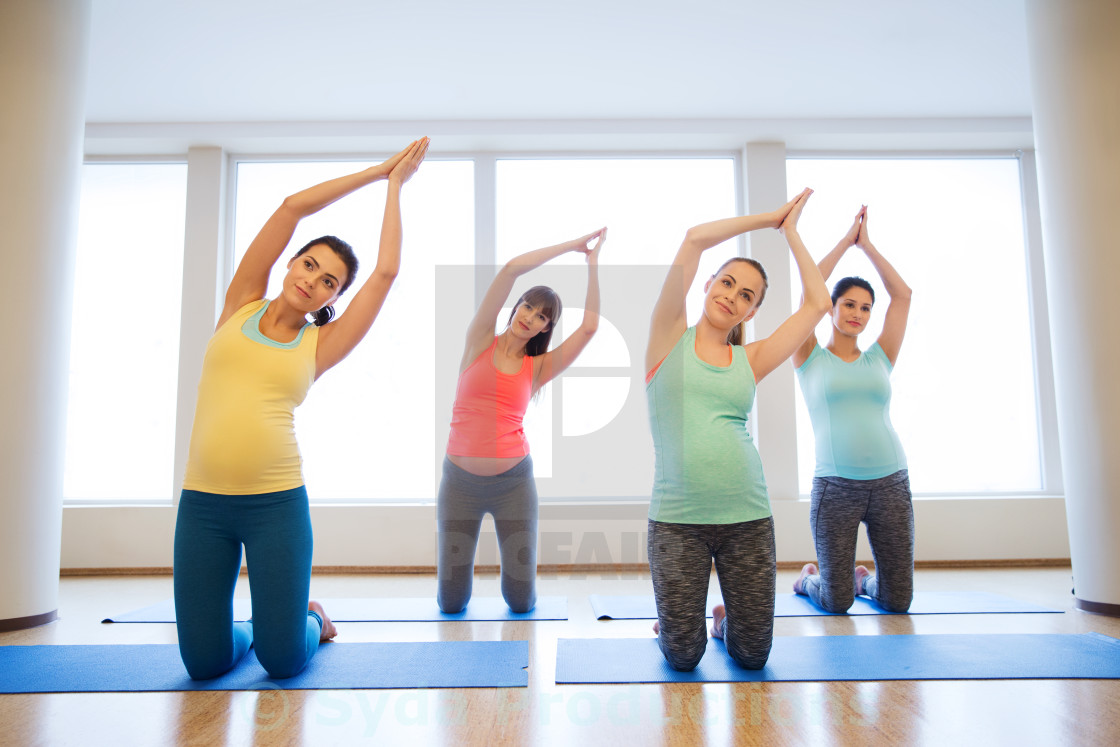 """happy pregnant women exercising on mats in gym"" stock image"
