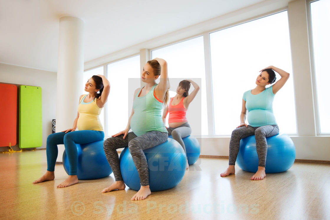 """""""happy pregnant women exercising on fitball in gym"""" stock image"""