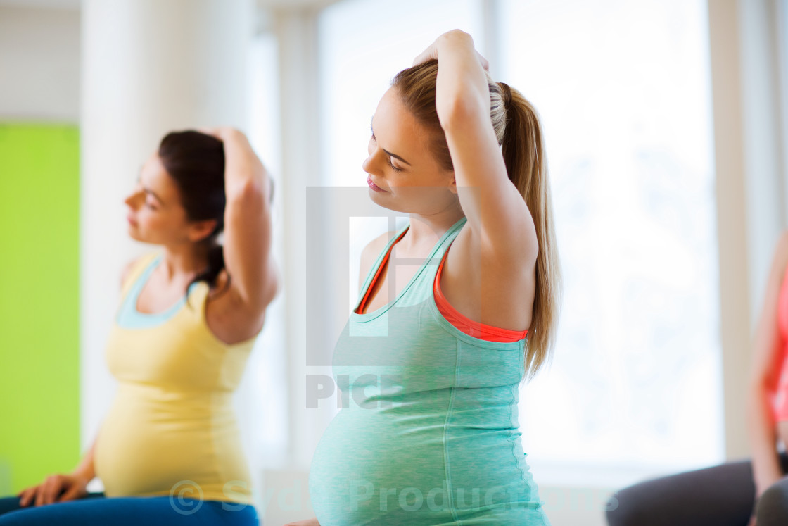 """""""happy pregnant women exercising in gym"""" stock image"""