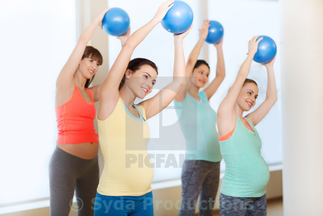 """happy pregnant women exercising with ball in gym"" stock image"