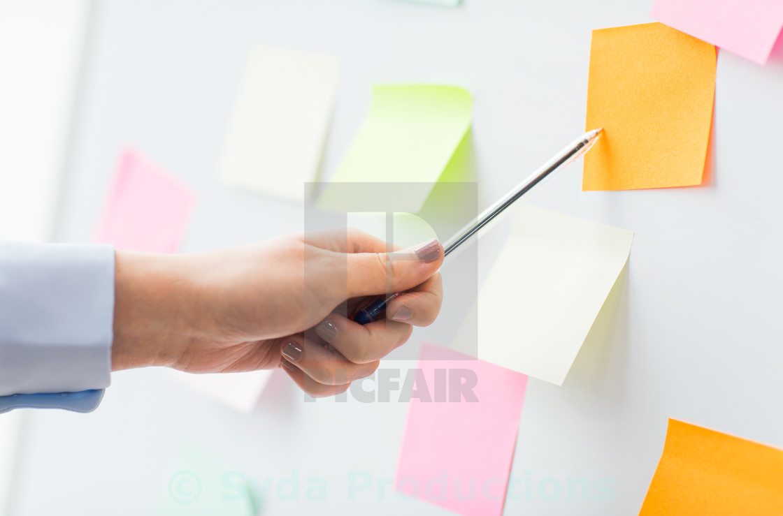 """""""close up of hand pointing to sticker on flip chart"""" stock image"""
