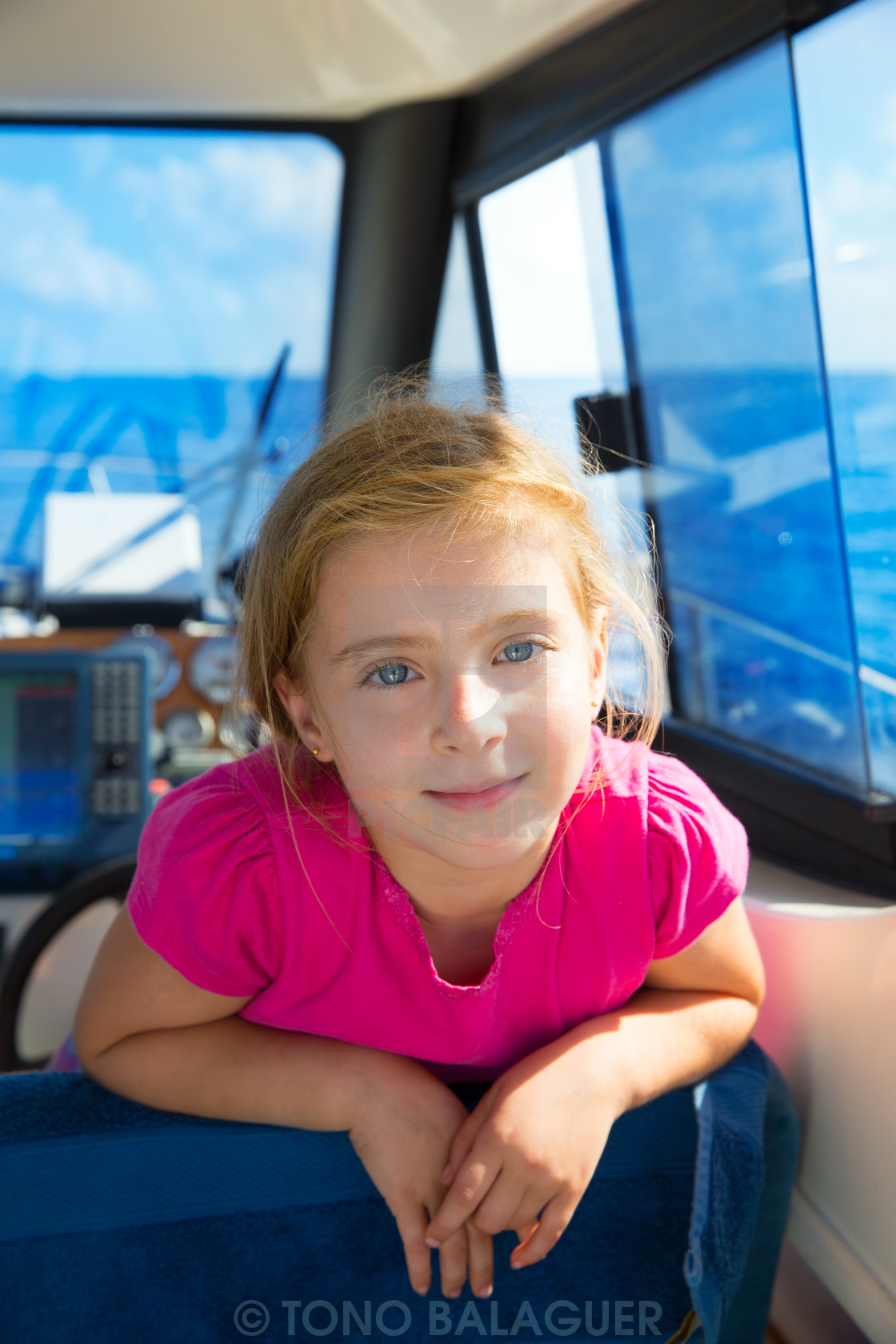 """Blond kid girl at boat indoor sailing smiling happy"" stock image"