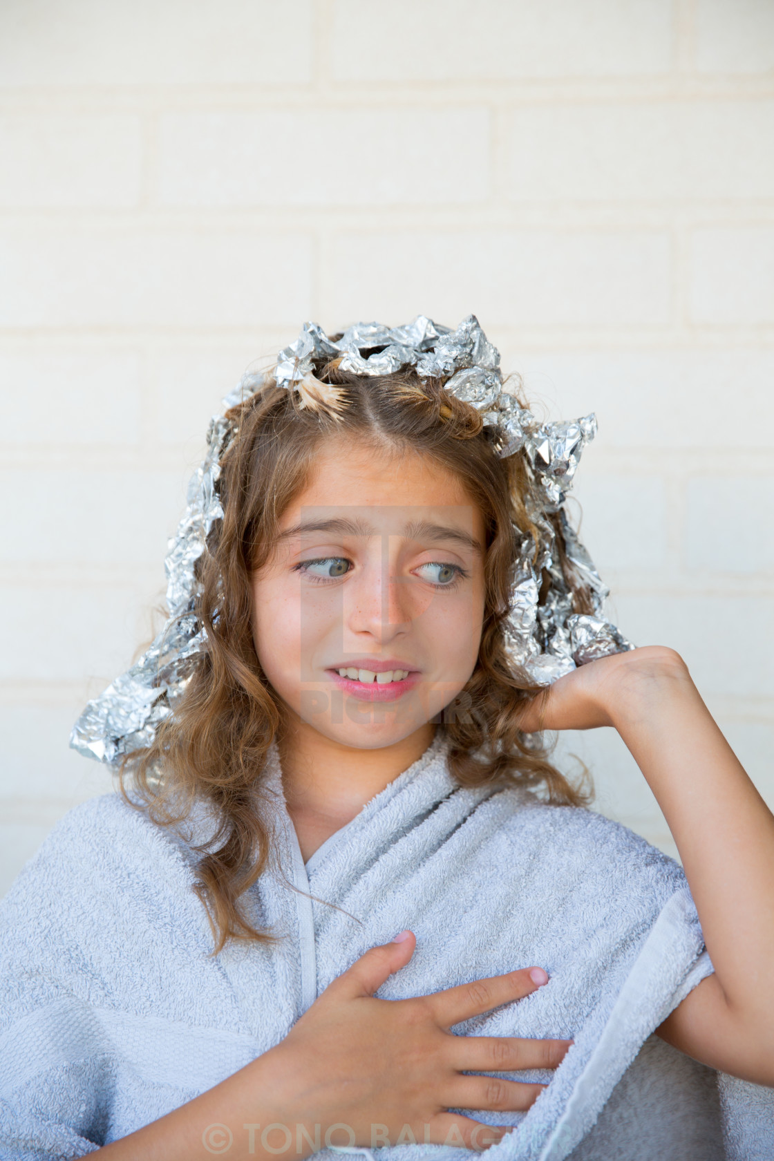 """""""Funny kid girl scared about his dye hair with foil"""" stock image"""
