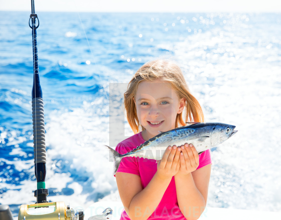 """Blond kid girl fishing tuna little tunny happy with catch"" stock image"