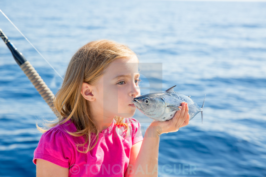 """""""Blond kid girl fishing tuna little tunny kissing for release"""" stock image"""