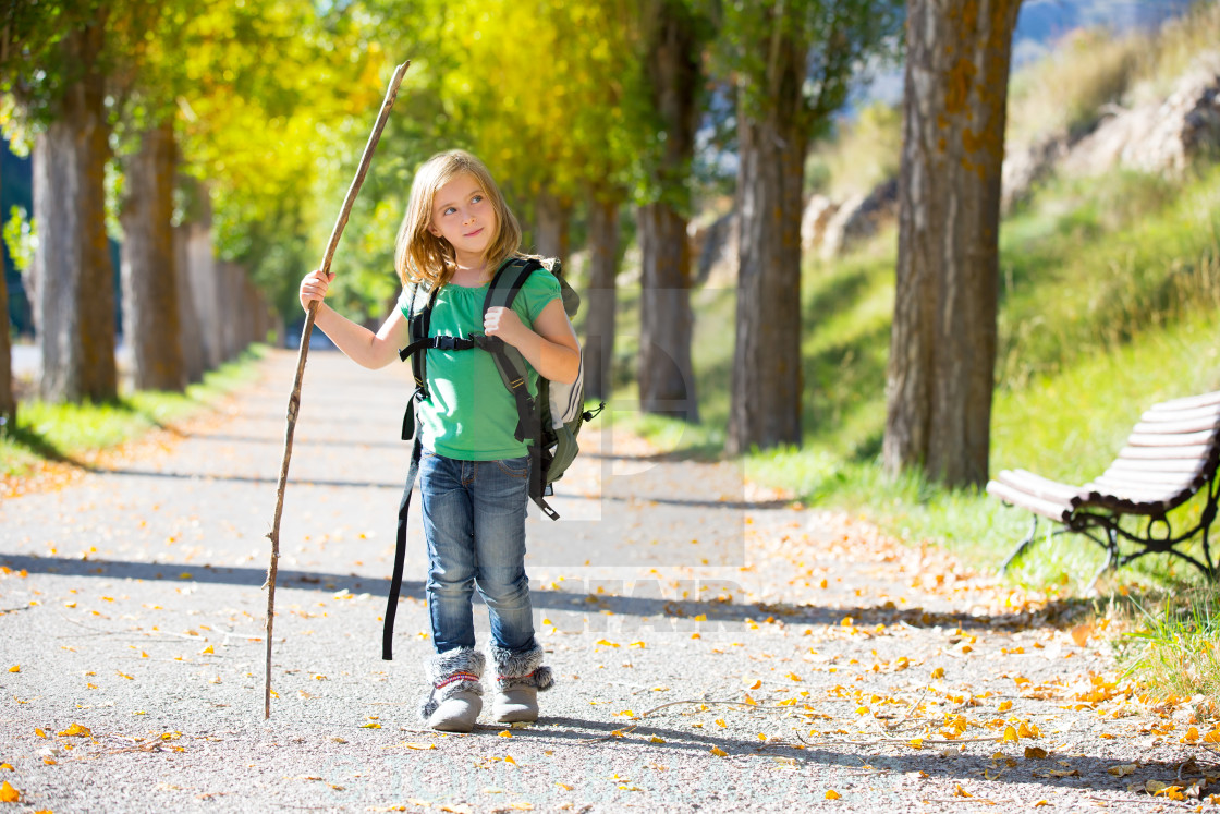 """Blond explorer kid girl walking with backpack in autumn trees"" stock image"