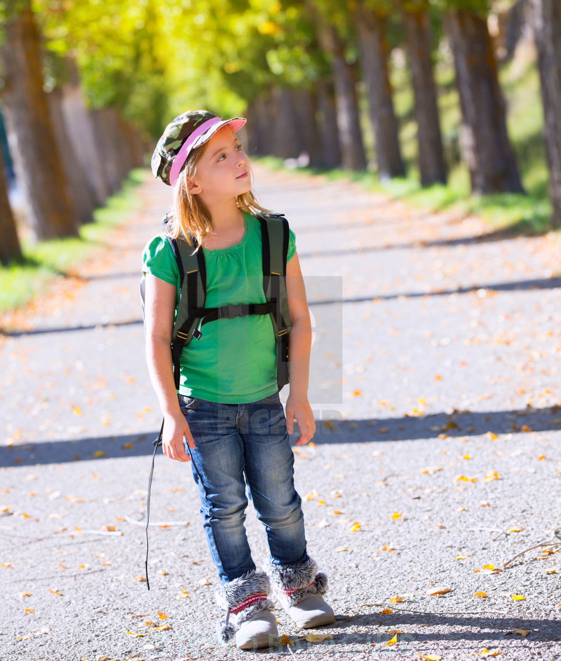"""""""Blond explorer kid girl walking with backpack in autumn trees"""" stock image"""